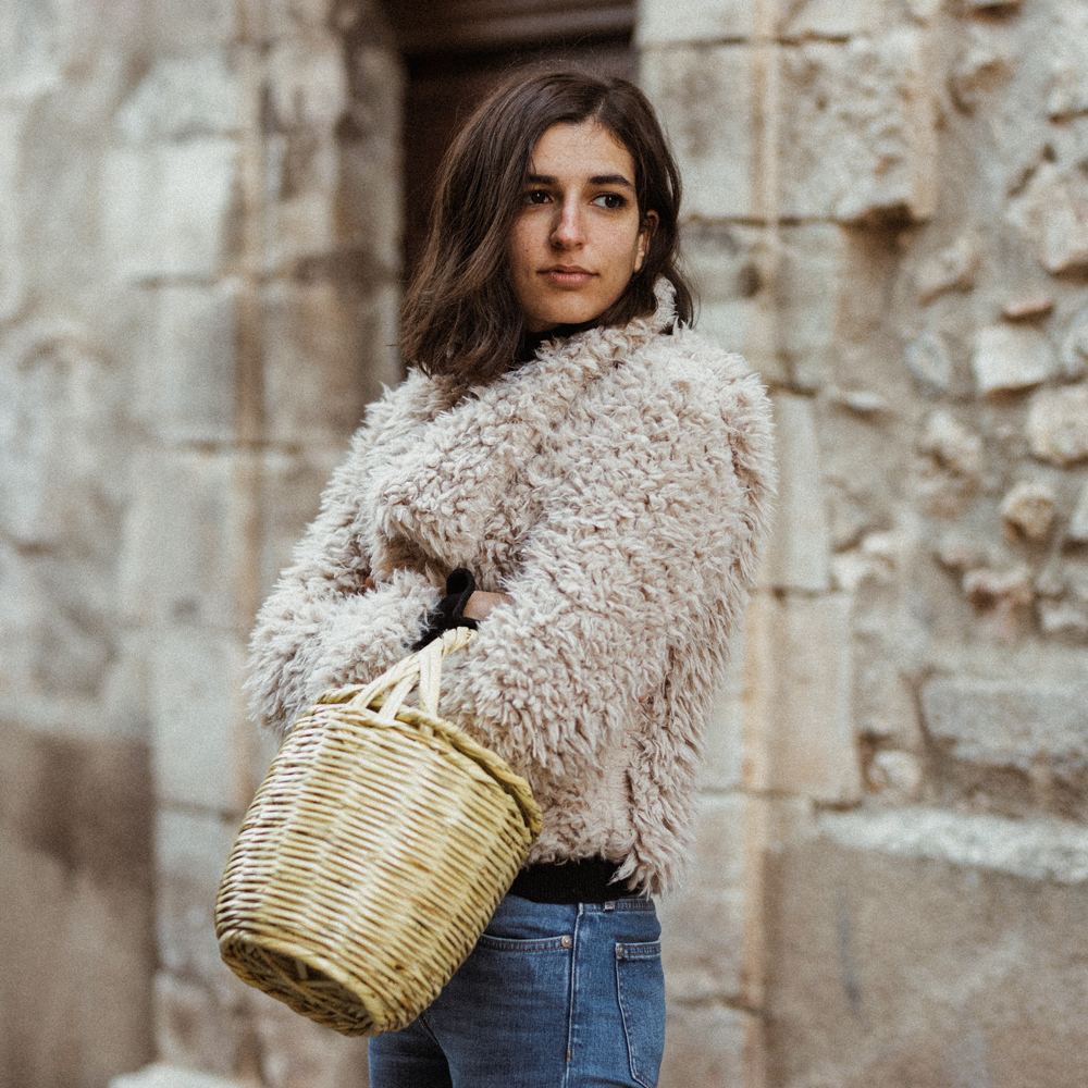 A fluffy coat and a basket bag