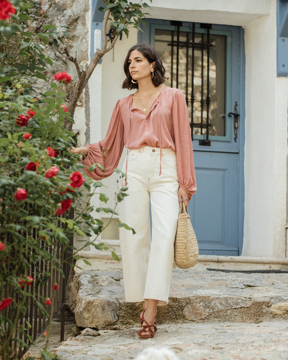 A flowy pink blouse and a pair of white jeans